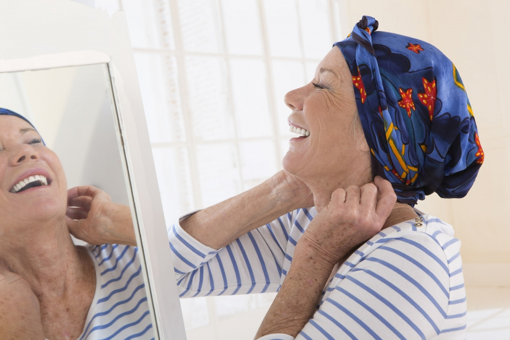 45633329 - senior woman looking at mirror and putting her scarf